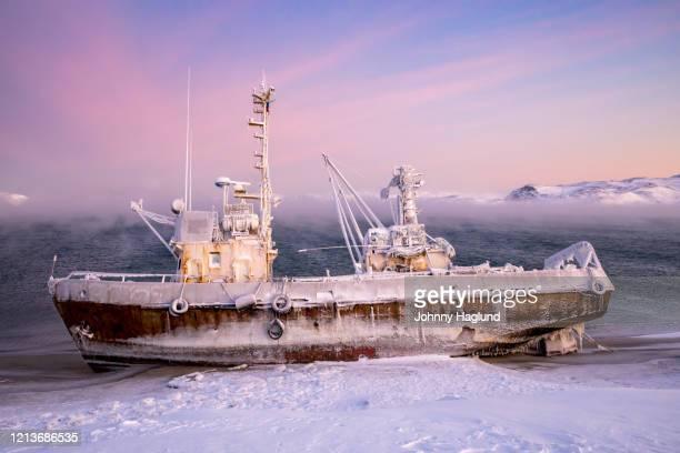 frozen fishing boat at the beach of the barents sea - eismeer stock-fotos und bilder