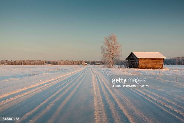 frozen house on snowy landscape against clear sky during winter - heinovirta stock pictures, royalty-free photos & images