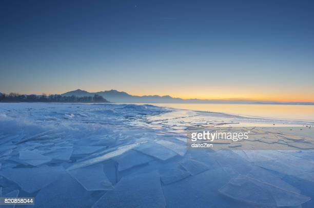 Frozen ice plates on shoreline of Lake Chiemsee in beautiful sunset light, Bavaria, Germany