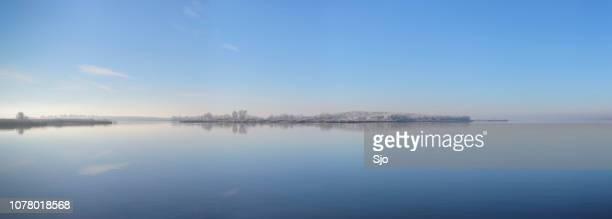 Frozen island in a calm winter lake landscape