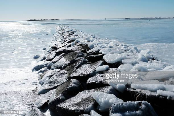 A frozen jetty stands in the icy waters of Long Island Sound as temperatures continue to stay below freezing in much of the Northeast on January 7...