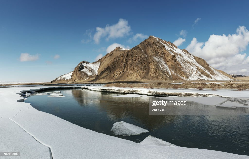 Frozen lake surrounded by snow on Bayanbulak,China : Stock Photo