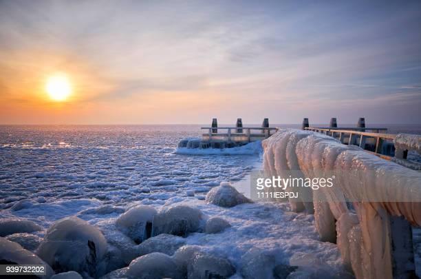 Bevroren meer met een ijzige steiger tijdens zonsopgang
