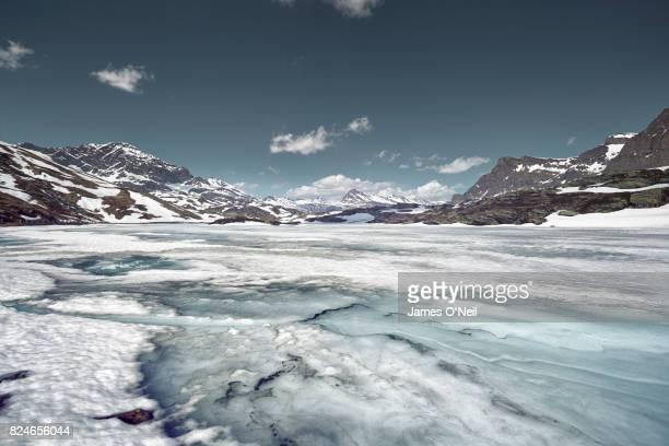frozen lake with distant mountain range, san bernardino, switzerland - schöne natur stock-fotos und bilder