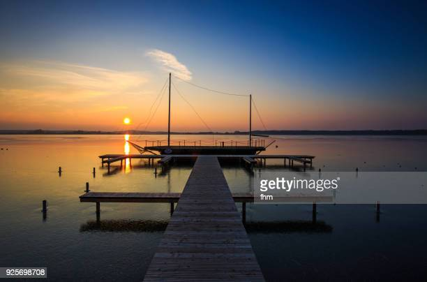 Frozen lake with jetty and ship at sunset (Brandenburg/ Germany)