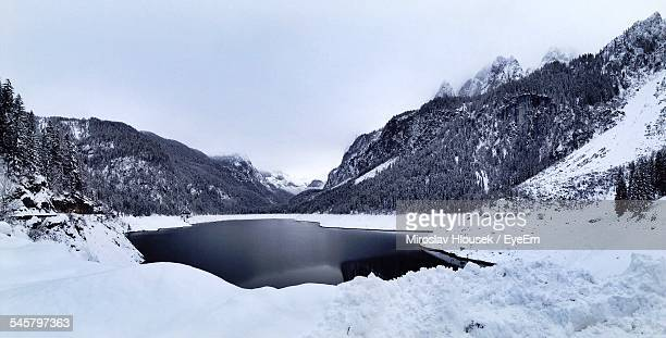 Frozen Lake With Mountains Against Clear Sky