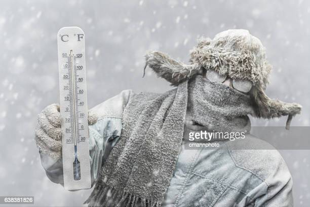frozen man holding a thermometer while it is snowing - kälte stock-fotos und bilder
