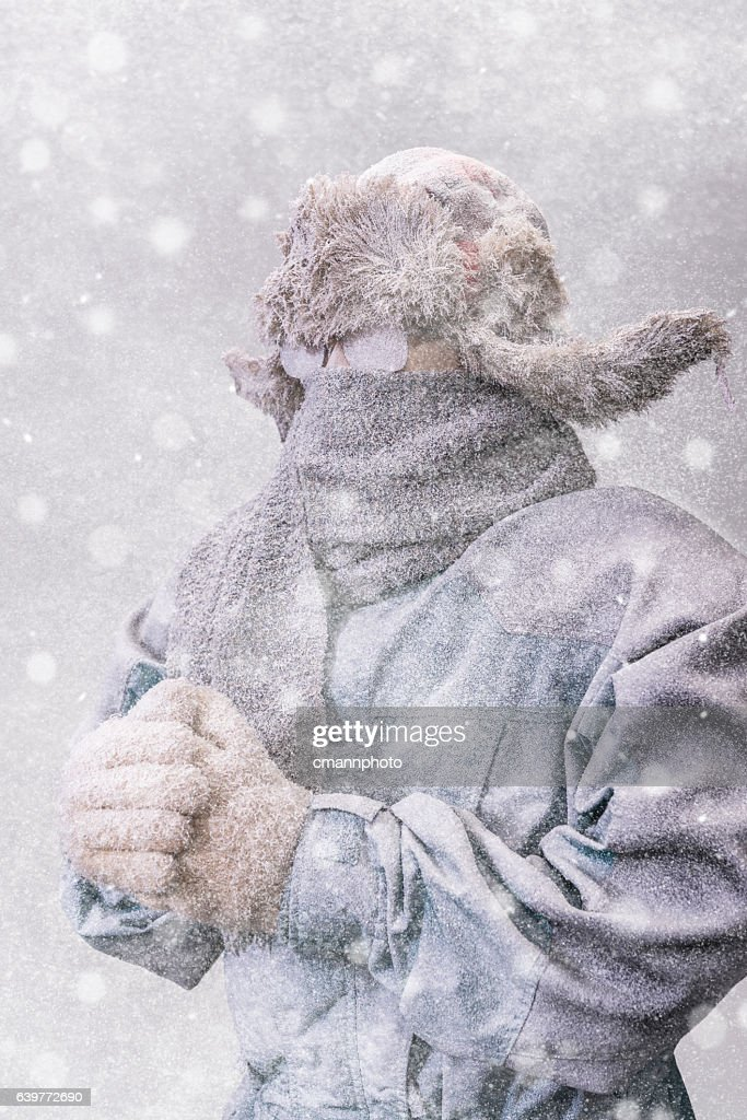Frozen man in parka, hat and scarf as snow falls : Stock Photo