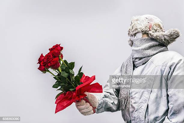 Frozen man presenting a bouquet of  a dozen red roses