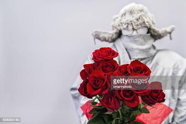 Frozen man presenting a bouquet of  a dozen red roses