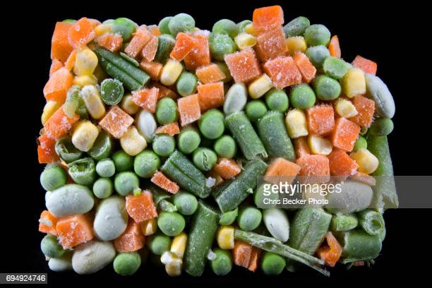 Frozen mixed vegetables out of box on black background