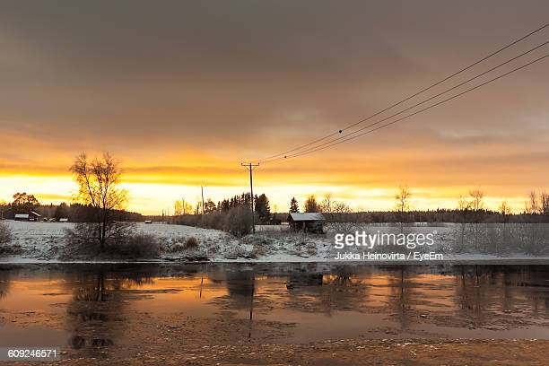 frozen river against cloudy sky at sunset - heinovirta stock photos and pictures