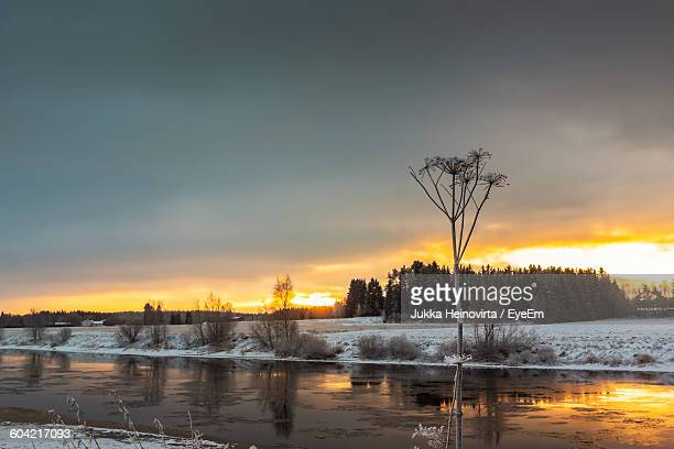 frozen river against cloudy sky during sunset - heinovirta stock pictures, royalty-free photos & images