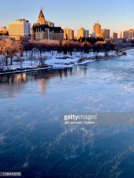 frozen river by buildings against clear sky during sunset - saskatoon stock pictures, royalty-free photos & images