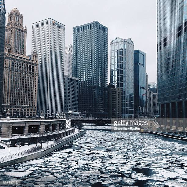 frozen river by skyscrapers - chicago river stock pictures, royalty-free photos & images
