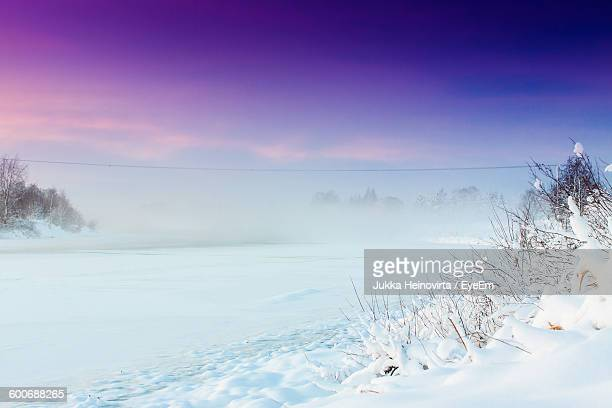 frozen river during purple sunset - heinovirta stock photos and pictures