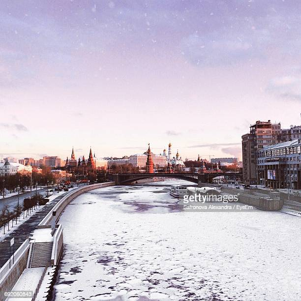 Frozen River In City Against Sky During Sunrise