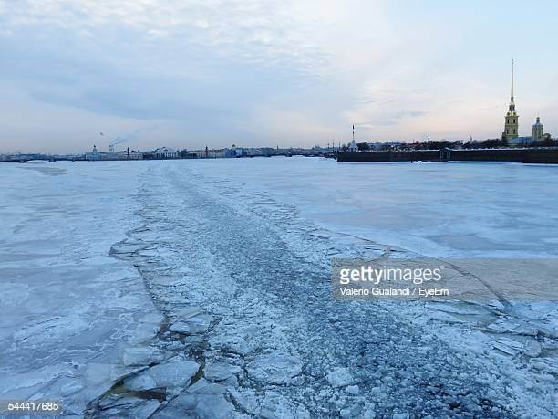 frozen river with peter and paul fortress in background against cloudy sky - peter forte - fotografias e filmes do acervo
