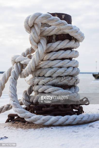 frozen ship cable under snow, old bollard at the pier in winter - moored stock pictures, royalty-free photos & images