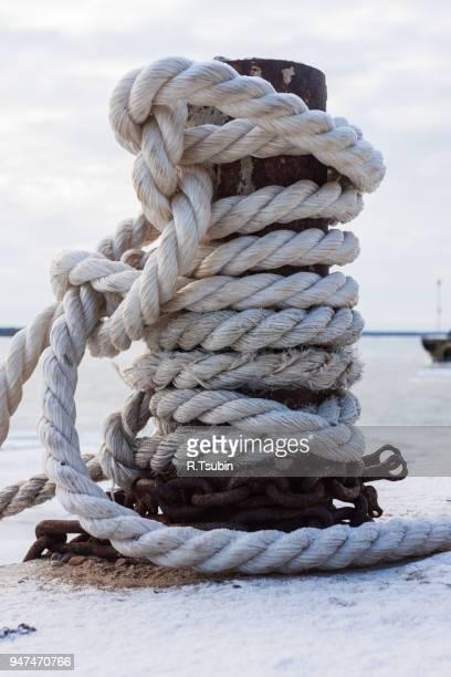 frozen ship cable under snow, old bollard at the pier in winter - vertäut stock-fotos und bilder