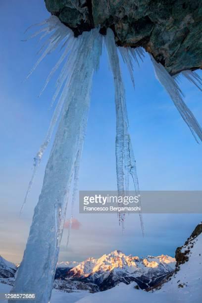 frozen waterfall with view on mount disgrazia, illuminates by sunrise. - italia stockfoto's en -beelden