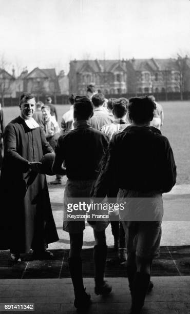 Frère David remettant un ballon de football à ses élèves pour un entraînement sportif au Saint Joseph's College circa 1950 à Londres RoyaumeUni