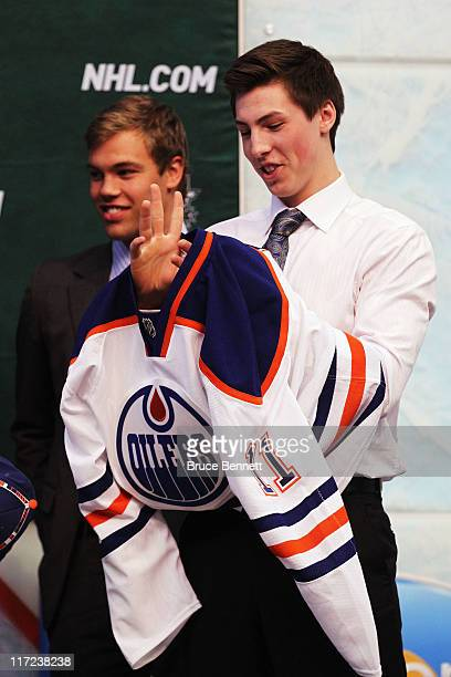 Frst overall pick Ryan NugentHopkins of the Edmonton Oilers puts on an Edmonton Oilers jersey as 2010 first overall pick Taylor Hall looks on in the...
