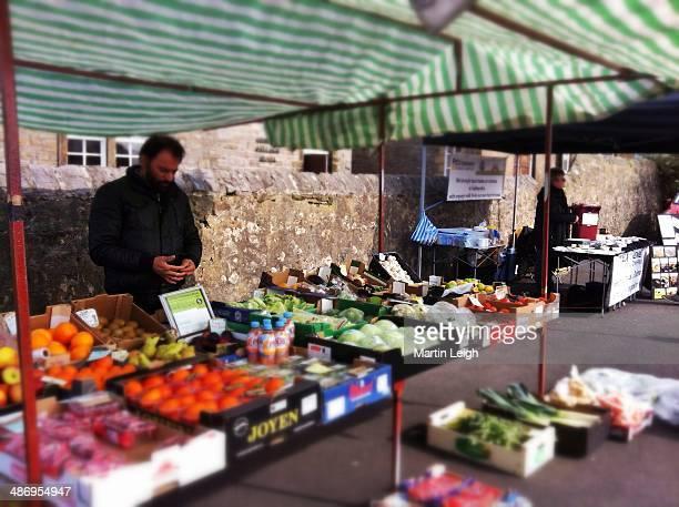 Fruit and veg stall holder at farmers market uk