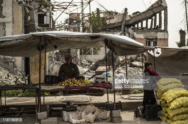 Fruit and vegetable seller waits for customers in a makeshift shop set in front of destroyed buildings in the northern Syrian city of Raqa, the...