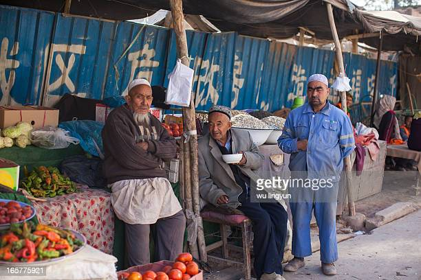 Fruit and vegetable stand owner with his friends on Kashi's street food market.
