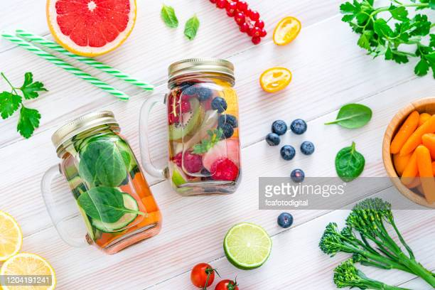 fruit and vegetables infused water on white table - infused water stock pictures, royalty-free photos & images