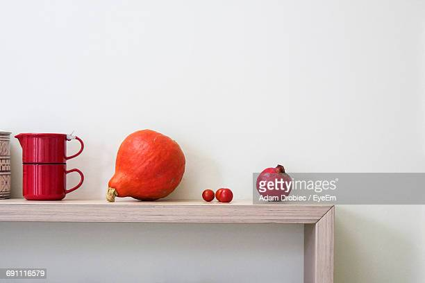 fruit and vegetables on shelf against white wall - red kettle stock photos and pictures