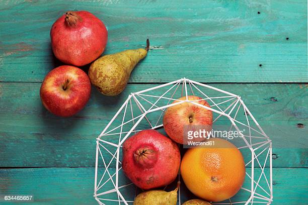 Fruit basket with pear, grapefruit, pomegranate and apple on wood