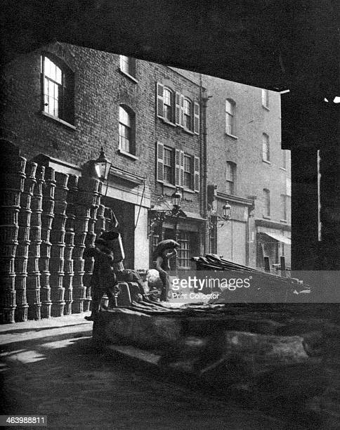 Fruit baskets piled against houses at Borough Market London 19261927 From Wonderful London volume II edited by Arthur St John Adcock published by...