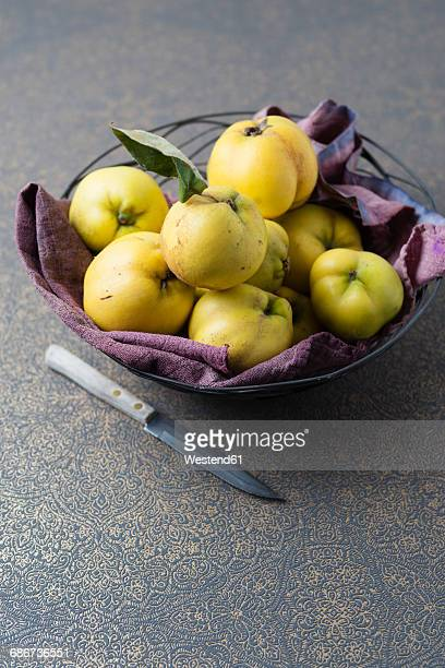 Fruit bowl of quinces and a knife