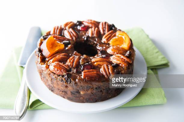 fruit cake with pecans on plate - fruit cake stock pictures, royalty-free photos & images
