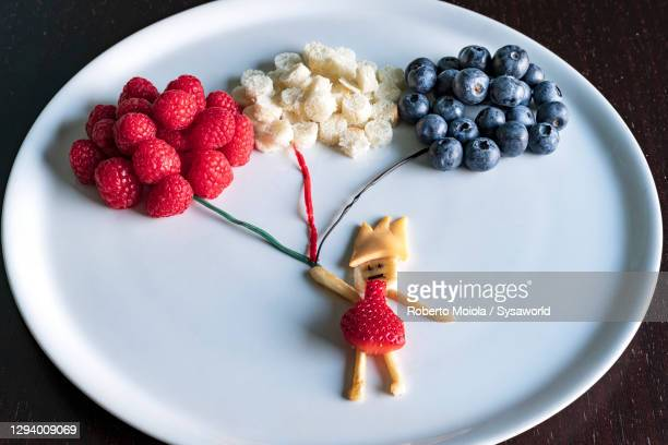 fruit creation of child holding balloons of berries in white plate - royal person stock pictures, royalty-free photos & images
