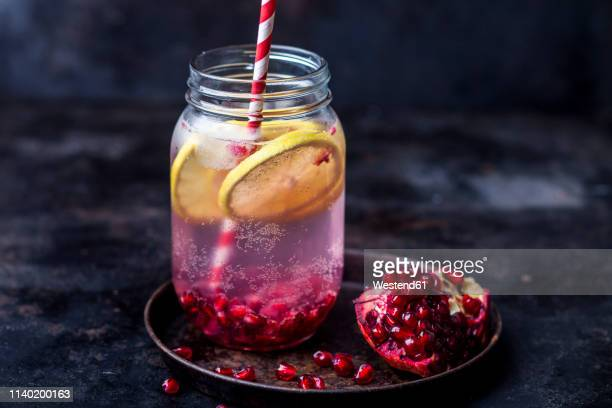 fruit infused water with lemon slices, crushed pomegranate seeds and sparkling water - kaltes getränk stock-fotos und bilder