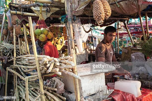 Fruit juice vendor looks up as he prepares a drink in Hyderabad, India, 2008