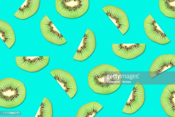 fruit pattern of kiwi slices on a blue background - kiwi fruit stock pictures, royalty-free photos & images