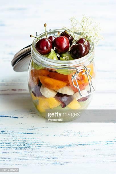 Fruit salad in jar with grapes, mango, banana, cherries, apricot, kiwi,