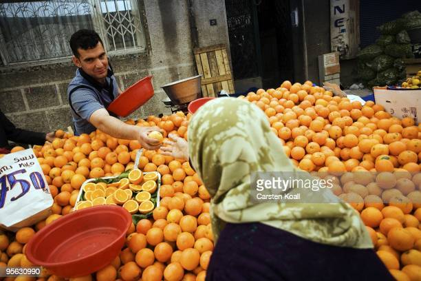 Fruit seller offers oranges to a scarfed woman on the weekly market in the district Tarlabasi on May 14, 2006 in Istanbul, Turkey. Tarlabasõ is a...