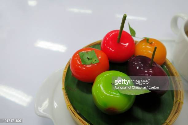 fruit shaped mung beans, kanom look choup, served on banana leaf plate. thai dessert concept. - aungsumol stock pictures, royalty-free photos & images