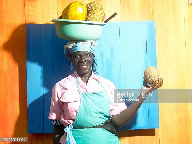 Fruit vendor balancing bowl of fruit on head, smiling, portrait