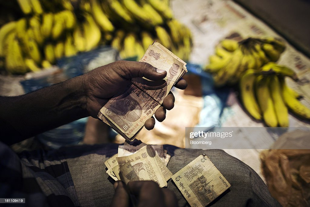 A fruit vendor counts rupee banknotes of various denominations at his stall in the old Delhi area of New Delhi, India, on Wednesday, Sept. 18, 2013. The Federal Reserves decision to postpone its rollback of U.S. stimulus offered Asian policy makers extra time to address domestic economic fragilities as the region copes with diminished capital inflows. Photographer: Prashanth Vishwanathan/Bloomberg via Getty Images