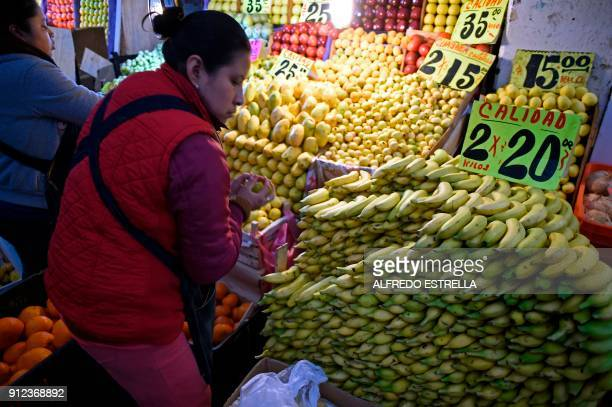 A fruit vendor displays her wares at the 'Central de Abasto' wholesale market in Mexico City on January 30 2018 Until the first half of January...