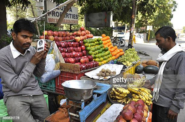 A fruit vendor enjoying live commentary of IndiaBangladesh Cricket World Cup 2015 match on radio on March 19 2015 in Ghaziabad India Indian captain...