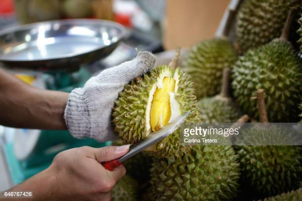 fruit vendor opening a fresh durian - durian stock pictures, royalty-free photos & images