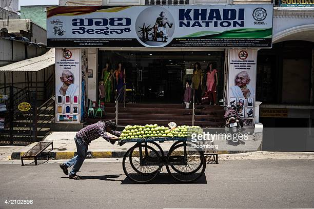 A fruit vendor pushes a cart past the Khadi Nation store in the Malleswaram district of Bangalore India on Sunday May 3 2015 India's Finance Minister...
