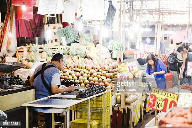 Fruit vendor reading the paper at the Mercado de la Merced in Mexico City.